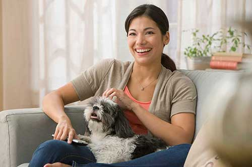 Woman holding her dog on a couch