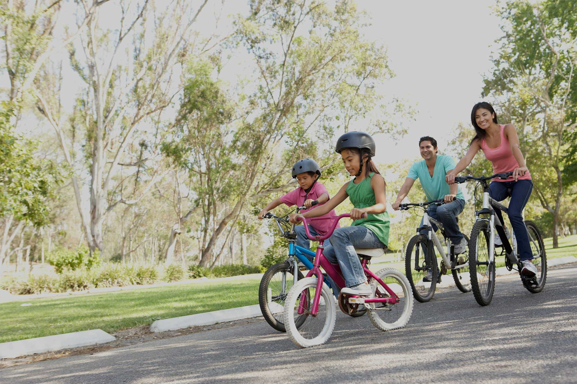 Family on bicycles riding through the park