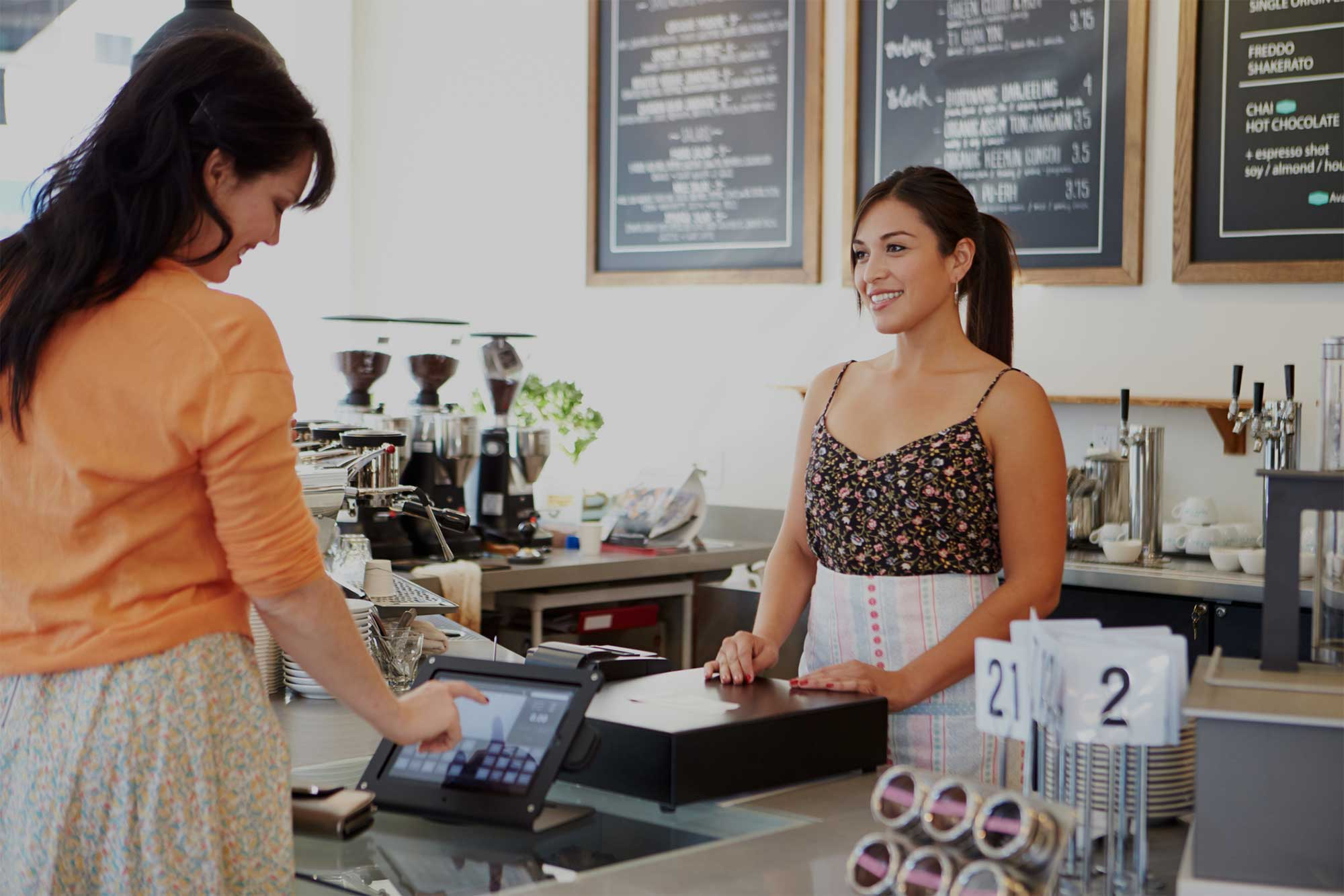 Woman standing at a counter in front of a cashier at coffee shop